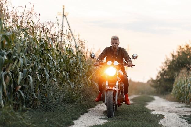 ミリタリージャケットを着た残忍な男がトウモロコシ畑で光のあるバイクに乗る