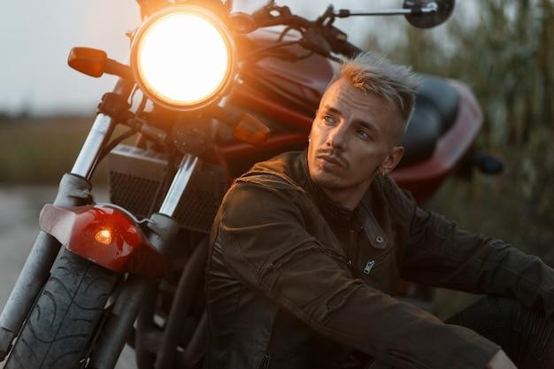 군사 재킷을 입은 잔인한 남자가 저녁에 들판에서 빛으로 오토바이 근처에 앉아 쉬고 있습니다.