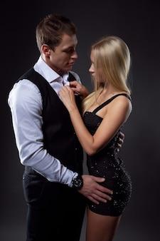 Брутальный влюбленный мужчина нежно обнимает сексуальную молодую блондинку