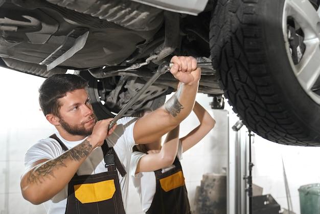 Зверский человек ремонтирует автомобиль с женщиной в автосервисе.