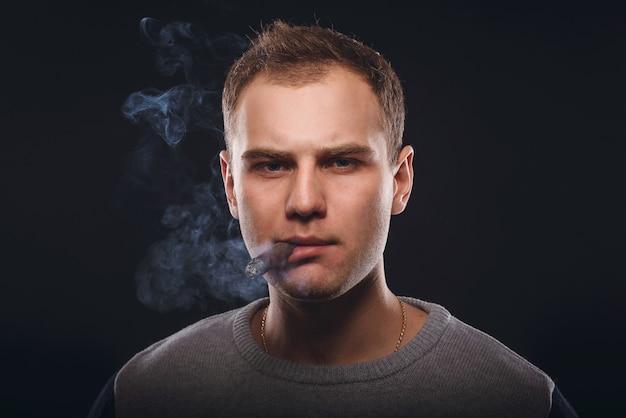 Брутальный мужчина курит сигару и выдувает дым