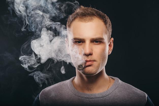 Brutal man smoking a cigar and blowing smoke
