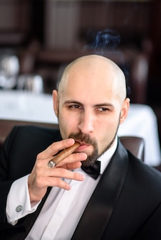 A brutal man in a suit smokes a cigar.