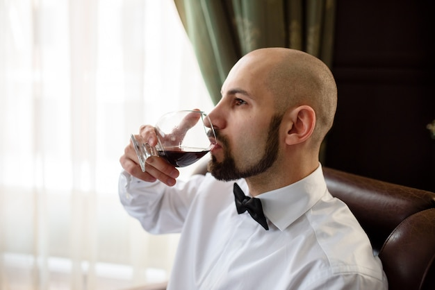 A brutal man tasting cognac.