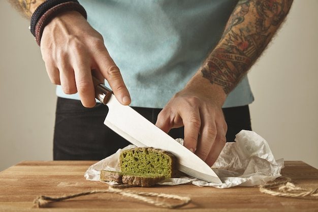 Uomo brutale tatuato mani tagliate spinaci sani fatti in casa pane rustico verde con coltello vintage sulle fette. tavolo in legno bianco