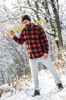 Brutal man with beard and moustache on winter day, snowy forest.  lumberjack in the woods with an ax.