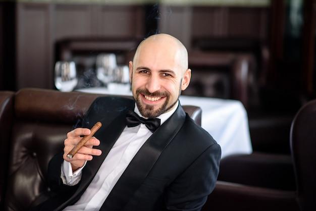 Brutal man with cigar laughs