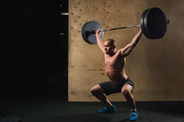 바벨 수염 기차와 잔인한 근육 남자 체육관에서 머리 위로 제기