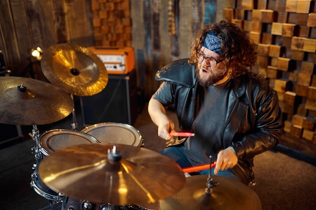 ドラムキットの背後にいる残忍なミュージシャン、ステージで演奏する音楽。ロックバンドの演奏またはガレージでの繰り返し、楽器を持った男、ライブサウンドパフォーマー
