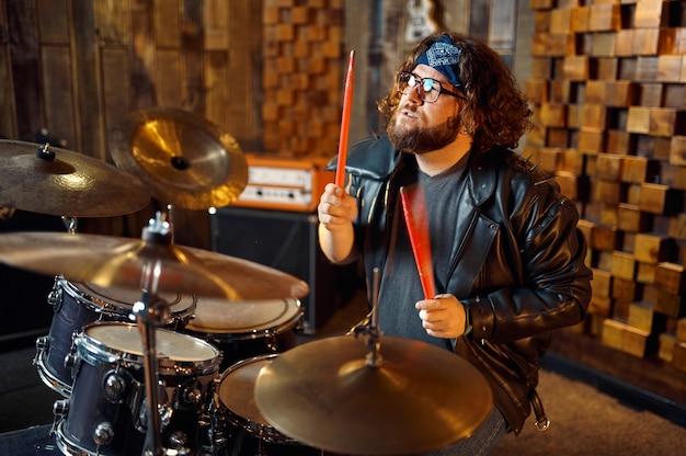 ステージ上のドラムキットの後ろにいる残忍なミュージシャン