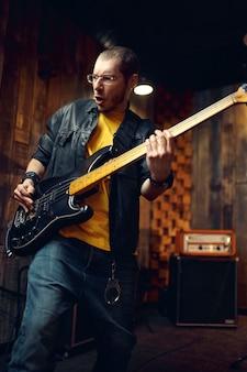 Брутальный музыкант с электрогитарой, исполняющий музыку на сцене. выступление рок-группы или повторение в гараже, мужчина со струнным музыкальным инструментом, живая музыка