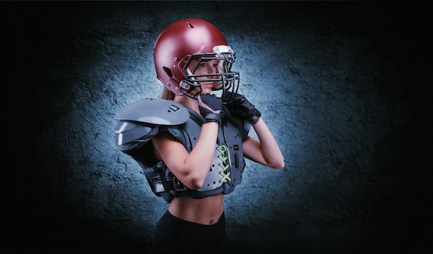 미식축구팀 선수의 유니폼을 입은 소녀의 잔인한 초상화. 장비 광고. 스포츠 개념입니다. 어깨 패드. 혼합 매체