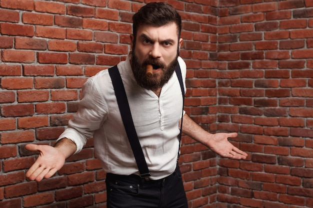 Brutal rage young handsome man smoking cigar on brick wall.