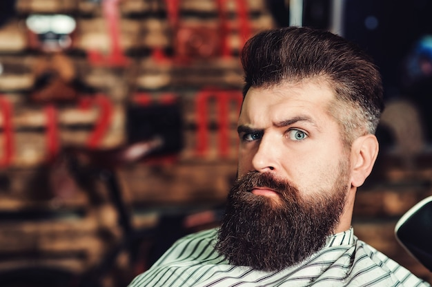 잔인한 심각한 젊은 수염된 남자. 이발소, 라이프 스타일 및 사람들 개념입니다. 이발소에서 수염 난된 남자입니다. 남자 헤어스타일, 수염 및 콧수염. 패션과 남성의 아름다움.
