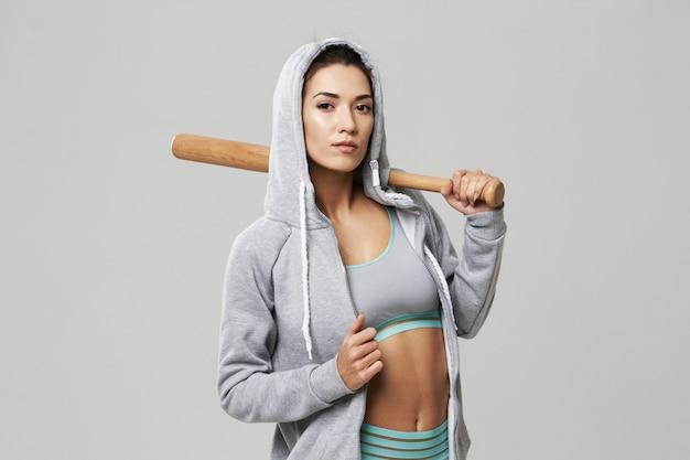 Brutal sportive woman in hood posing holding bit on white.