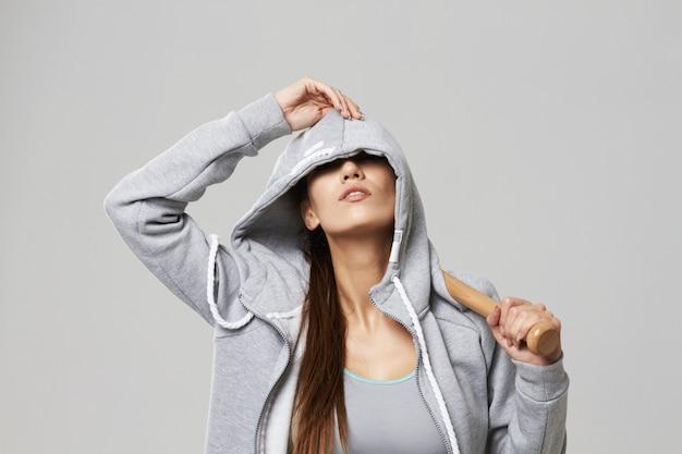 Зверская sportive женщина в клобуке представляя держащ бит на белизне.
