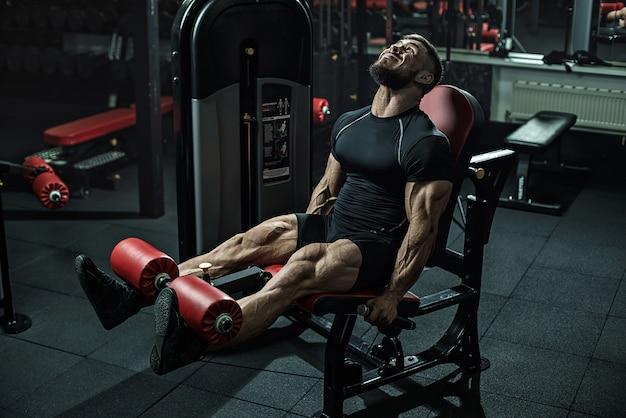 Brutal strong athletic men bodybuilder trains in the gym