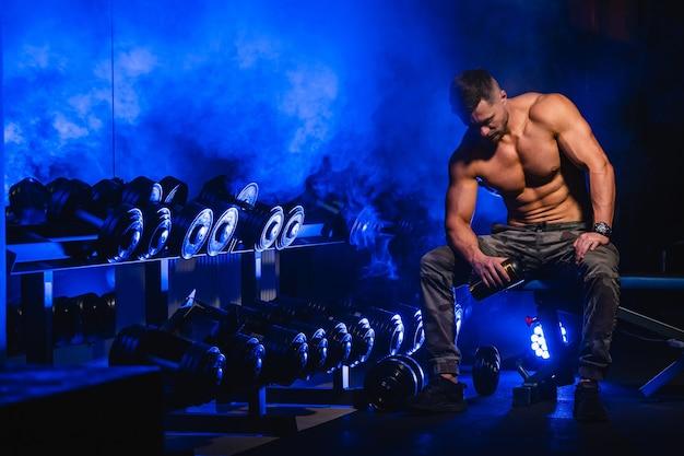 筋肉をポンピングする残忍な強い運動の男性。スポーツ用品のトレーニングを行う-裸の胴体を使用してジムでエクササイズを行う筋肉のボディービルダー。フィットネスとボディービルのコンセプト。
