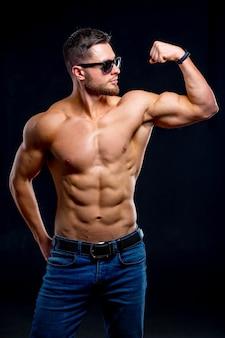 筋肉をポンピングする残忍な強い運動の男性。トレーニングとボディービルのコンセプト。裸の胴体を持つハンサムな男。フィットネスモデルがポーズをとっています。サングラスをかけています。