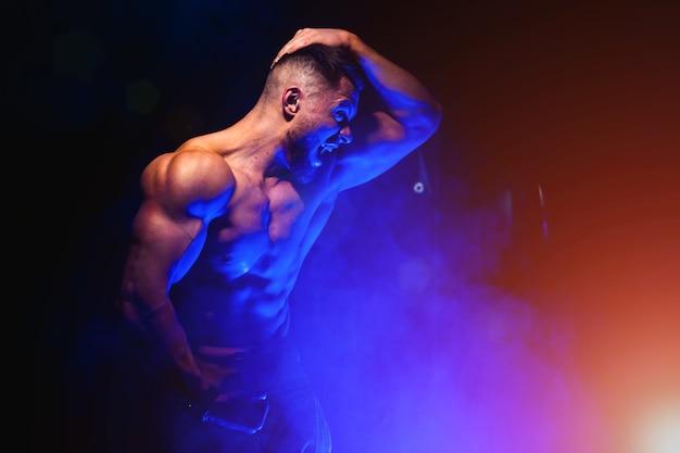 筋肉をポンピングする残忍な強い運動選手。トレーニングとボディービルのコンセプト