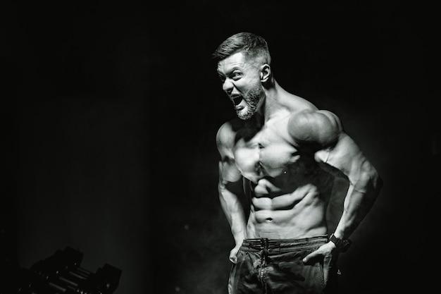 근육을 펌핑하는 잔인한 강한 운동 남자.