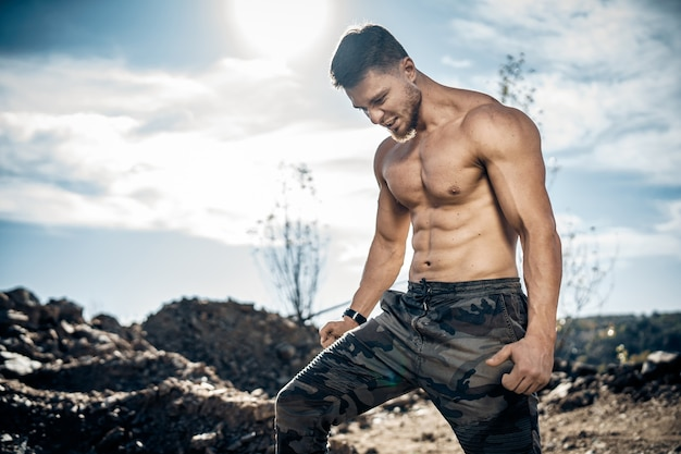 屋外でポーズをとる残忍な強いボディービルダー。採石場での写真撮影。アウトドアスポーツのコンセプト。筋肉のポーズとポンピング。自然の風景。