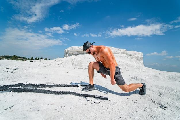 屋外でポーズをとる残忍な強いボディービルダー。採石場での写真撮影。アウトドアスポーツのコンセプト。ロープでポーズをとる。白い風景。