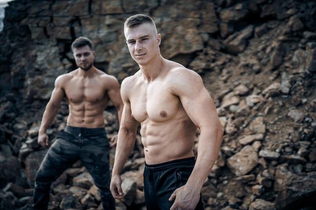 筋肉をポンピングする残忍な強力なボディービルダー。ボディービルとアウトドアスポーツのコンセプト。 2人の男性アスリート。