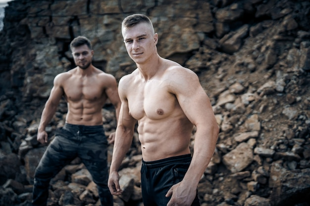 Brutal strong bodybuilders pumping up muscles. bodybuilding and outdoor sports concept. two male athletes.