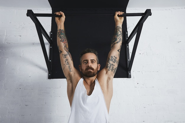 Брутальный татуированный спортивный мужчина в белой майке без надписи демонстрирует художественные движения крупным планом в классическом подтягивании. вешается на перекладине и смотрит в камеру.