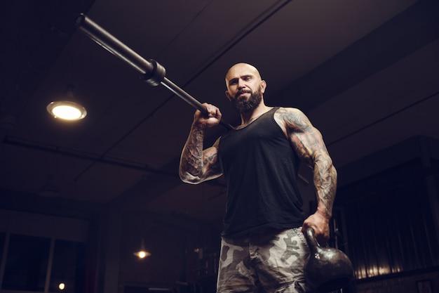 Жестокий татуированный бородатый мужчина в тренажерном зале