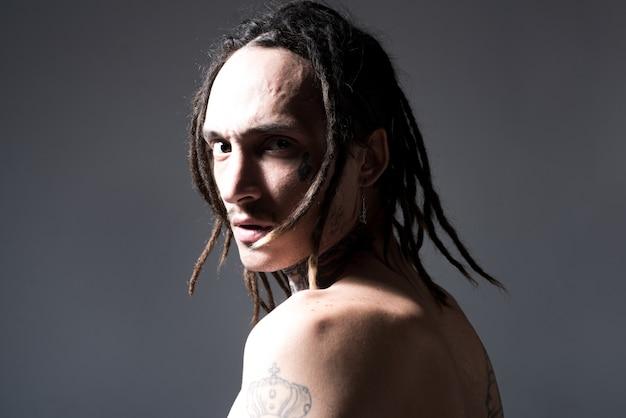 残忍な入れ墨の男。男のタトゥーファッション。残忍な男の肖像画。