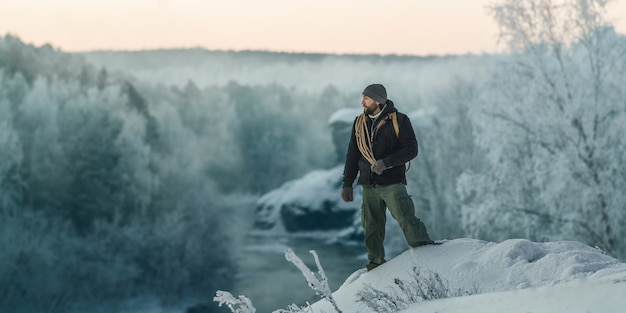 A brutal tourist man walks through a snow-covered forest against the background of a river and rocks at dawn