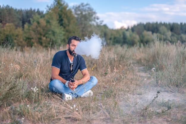 Жестокий вейп-мужчина курит электронную сигарету на открытом воздухе.