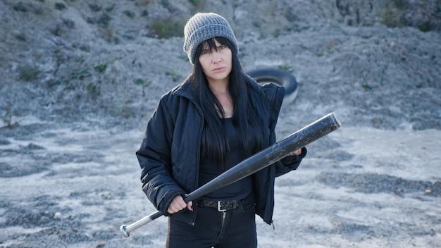 フーリガンギャングの残忍な女性が荒れ地で野球のバットを持って行きます。