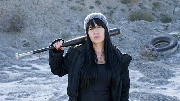 Brutal woman from hooligan gangs goes with a baseball bat in the wasteland.