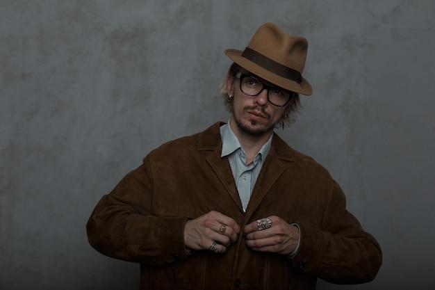 Брутальный молодой бородатый хипстер в модных круглых очках в элегантной шляпе на пуговицах классической рубашки в модном коричневом жакете