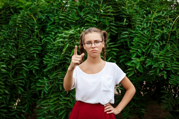Brutal young female student in glasses pointing finger at front