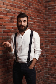 Brutal young handsome man smoking cigar on brick wall.