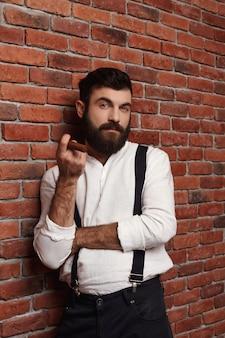 벽돌 벽에 잔인 한 젊은 잘 생긴 남자 흡연 시가.