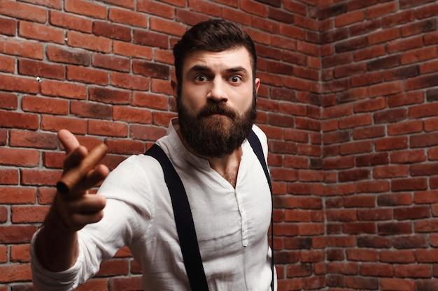レンガの壁に残忍な若いハンサムな男喫煙葉巻。