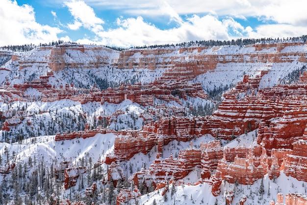 ブライスキャニオン、ユタ州、冬の山と赤い岩に雪が降る