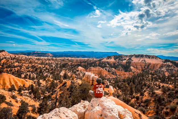 Национальный парк брайс, штат юта, сша мальчик с раскинутыми руками, наслаждающийся видами с санрайз-пойнт в брайсе.