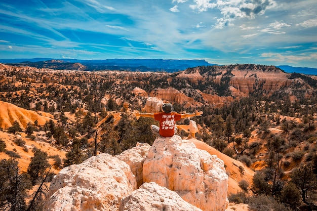 Bryce national park, utah  united states  a boy with arms outstretched enjoying the views from sunrise point in bryce