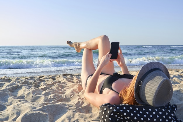 Красивая женщина, лежа на пляже и глядя на смартфон на море bsckground