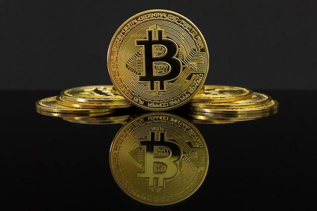 Зеркальное отражение большой золотой монеты btc. монета биткойн находится на черном столе и черном. золотой биткойн, сложенные.