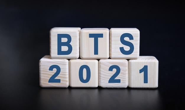 반사와 검은 배경에 나무 큐브에 bts 2021 텍스트.
