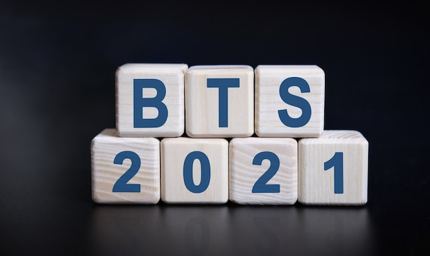 Bts 2021 text on wooden cubes on a black background with reflection.