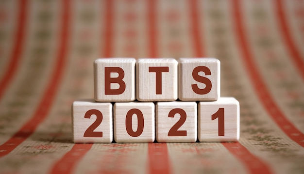 Bts 2021 text on wooden cubes on a monochrome background with reflection.