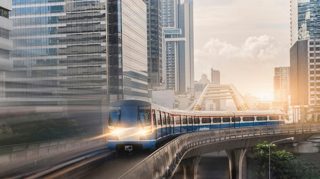 Bts skytrain, electric train, running on the way with business office buildings on the background.